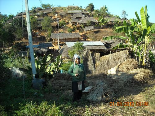 Akha Tribe Woman stands before her village